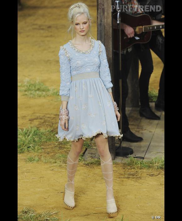 Chanel , Printemps-Eté 2010, Paris  Pour Chanel, le bleu joue les ambiances d'innocence et de fragilité. Une pâleur colorée, bleu givré, bleu sur-éclairci, associée au teint blanc et aux cheveux platine, qui crée une luminosité évanescente pour une image sage et passive.