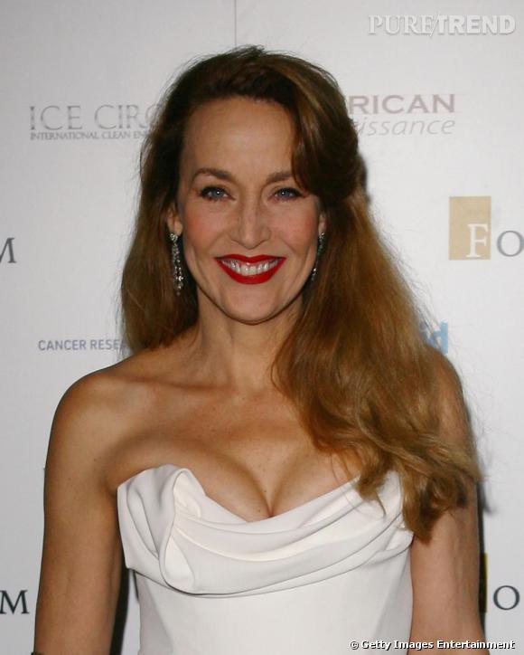 La magnifique Jerry Hall en robe blanche bustier au décolleté généreux.