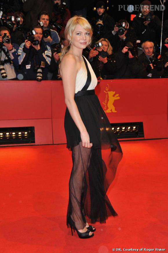 """Michelle Williams    L'actrice américaine a choisi une robe asymétrique bicolore"""", et a craqué pour les très classiques escarpins """"Epines"""" en satin noir signés Roger Vivier."""