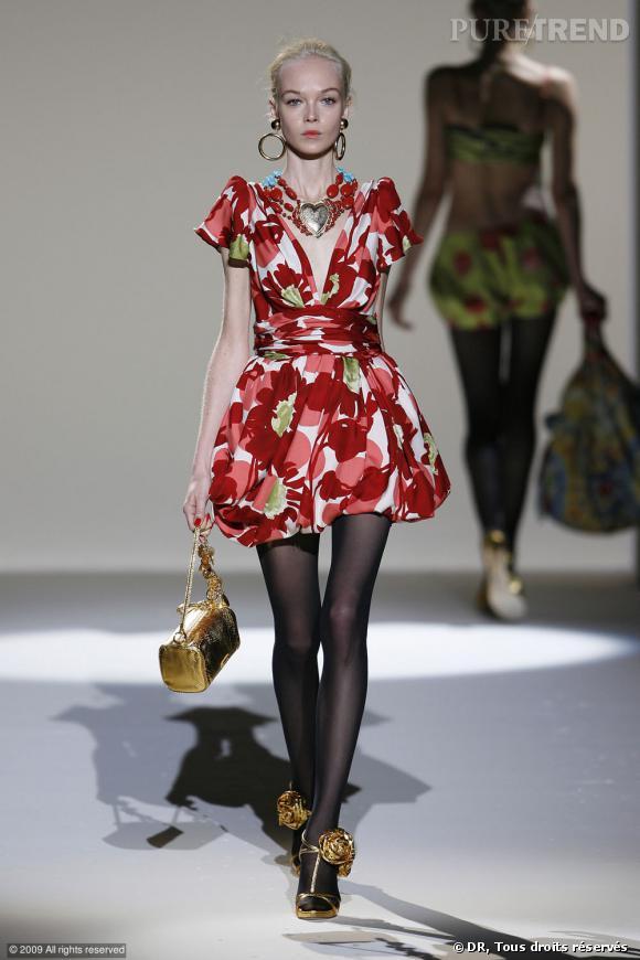 Défilé Moschino Printemps-Eté 2010       Du rouge vif sur une robe aux épaules structurées qui donne des airs de lolita bling-bling avec des accessoires dorés ou oversized.
