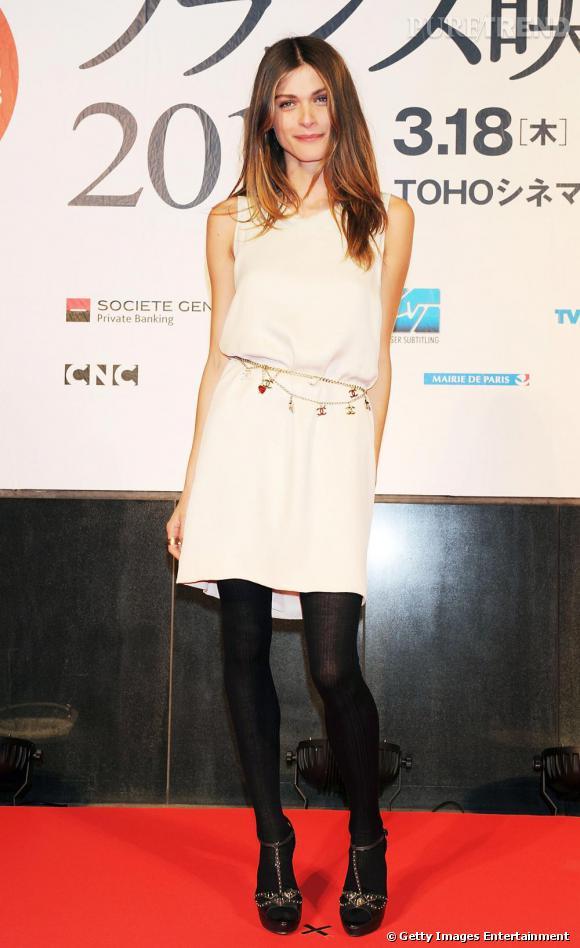 Robe blanche sur collants noirs, Elisa Sednaoui épouse merveilleusement les codes de la maison Chanel.