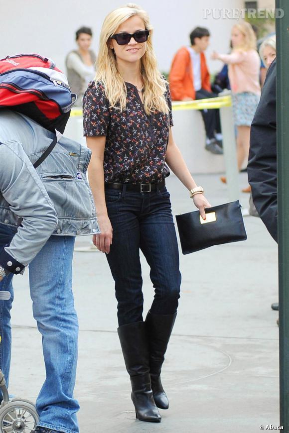 Jean brut + bottes noires + blouse imprimée : Reese Witherspoon mixe confort et style.