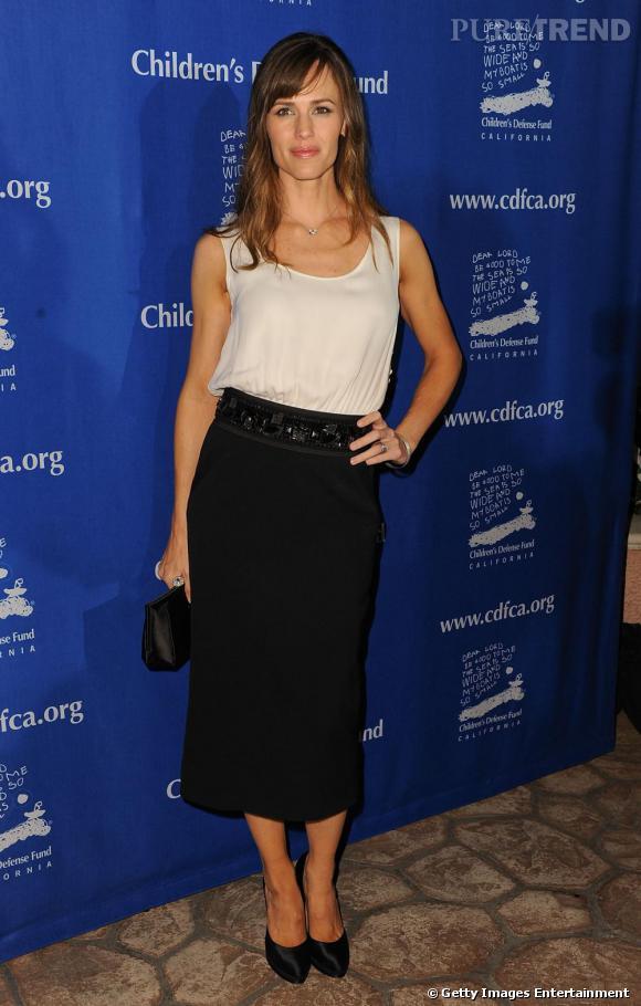 Minimalisme chic pour Jennifer, vêtue d'un top fluide en soie qui dédramatise l'esprit 50's de sa jupe mi-longue.