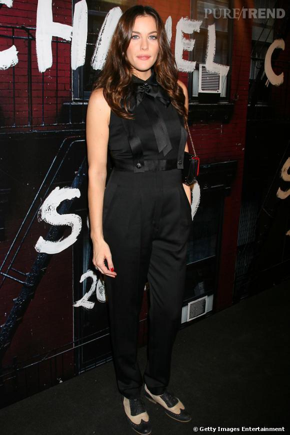 Liv Tyler suit la cadence, vêtue d'une combi-pantalon masculin-féminin, tendance qu'elle accentue par des derbys bicolores.