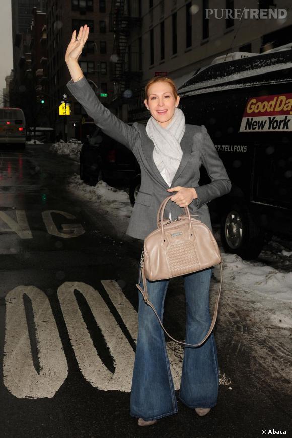 Blazer gris, écharpe plus claire et jean 70's, Kelly Rutherford reste classique. Une tenue pimentée par son sac taupe, une de ses propres créations.