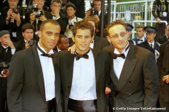 Comment on se coiffait dans les années 90 ?        Nom  : 2be3       Coiffures  : le crâne rasé d'Adel et les pattes sur le côté, les cheveux ébouriffés au gel de Flip et le plaqué en arrière de Frank.