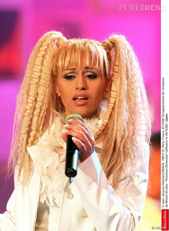 Comment on se coiffait dans les années 90 ?        Nom  : Lâam       Coiffure  : un blond platine, une frange, deux couettes et les cheveux gaufrés.