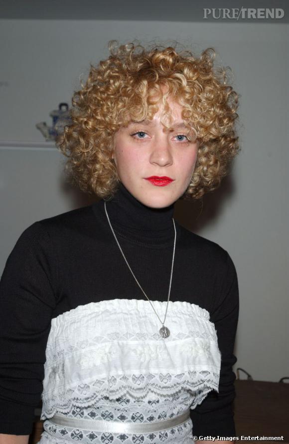L'évolution beauté de Chloë Sévigny Chevelure bouclée et bouche rouge fluo, l'actrice tente une extravagance capillaire.