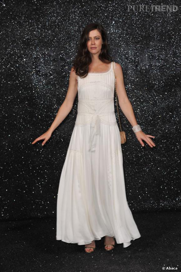 Anna Mouglalis, virginale, prend la pose devant le mur de paillettes.