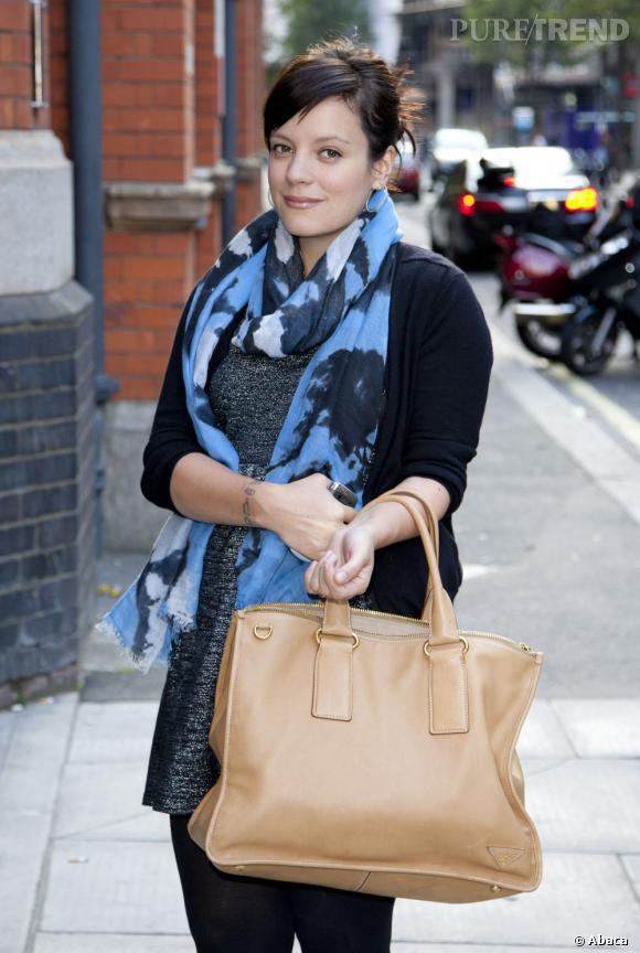 Lily Allen porte un foulard bleu et un sac crème pour donner de la couleur à son look.