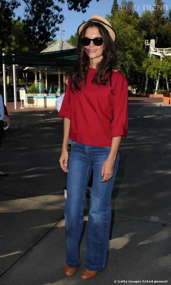 L'actrice porte une jean légèrement large et une blouse framboise.