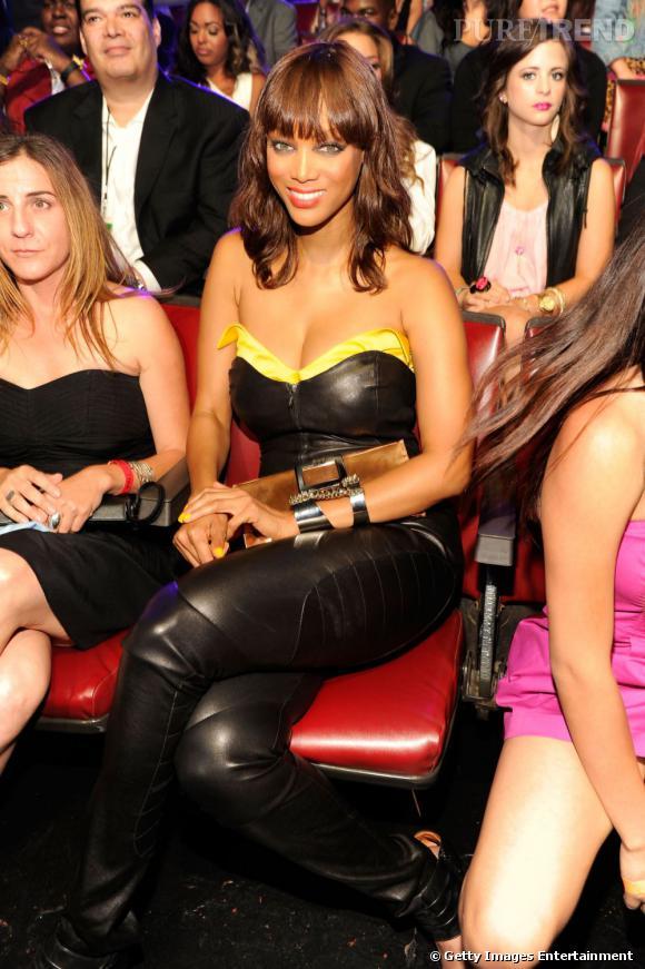 Dans le public, Tyra Banks se prête au jeu des photographes avec le sourire.