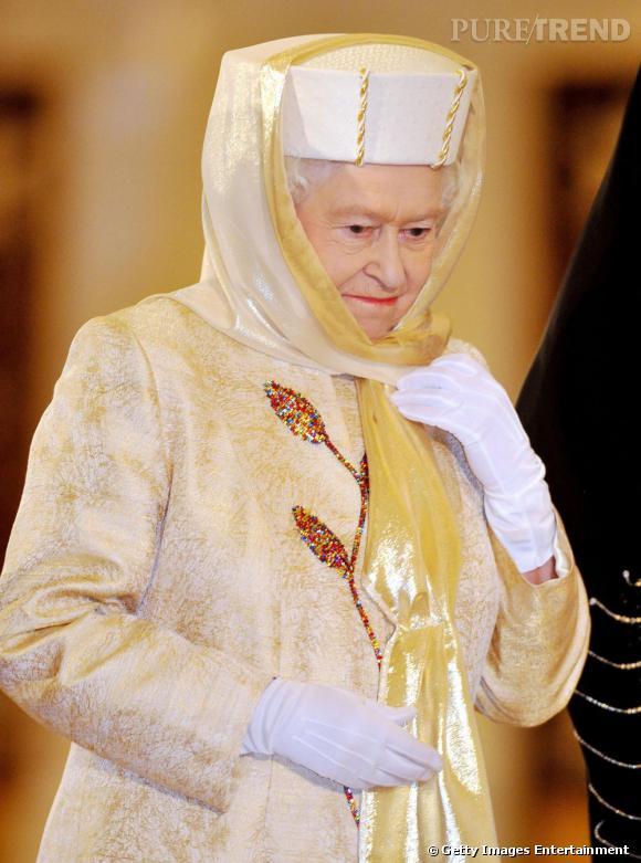 Consternée, la Reine Elizabeth II arbore une tenue traditionnelle du Moyen-Orient. On peut lire dans ses yeux qu'elle regrette déjà ses bibis colorés.