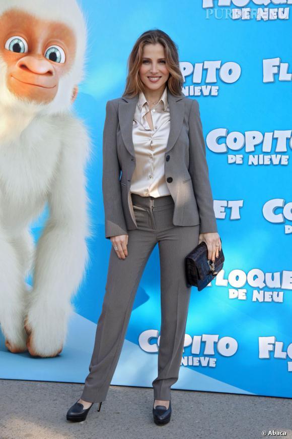 Elsa Pataky porte un tailleur pantalon oui, mais aussi des escarpins et une chemise en satin. Ouverte.