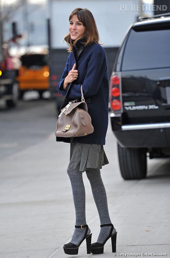 En cuir et marine, le manteau pimente son allure de jeune fille avec style.
