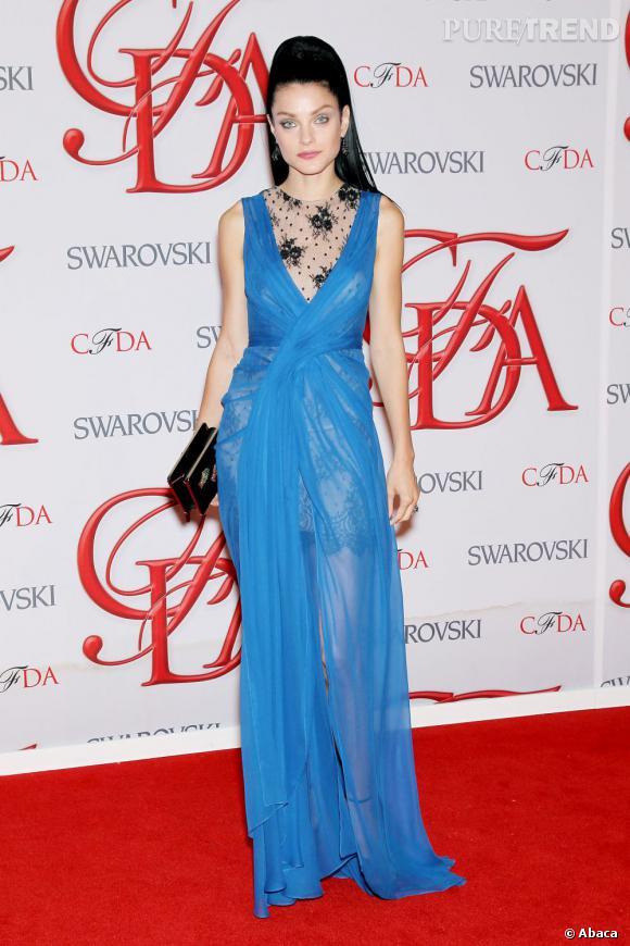 Jessica Stam porte une robe en voile bleu transparent, par dessus une courte robe en dentelle beige et noire.