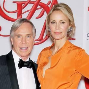 Tommy Hilfiger et sa femme Dee Ocleppo posent, l'un classique, l'autre flashy dans une robe orange