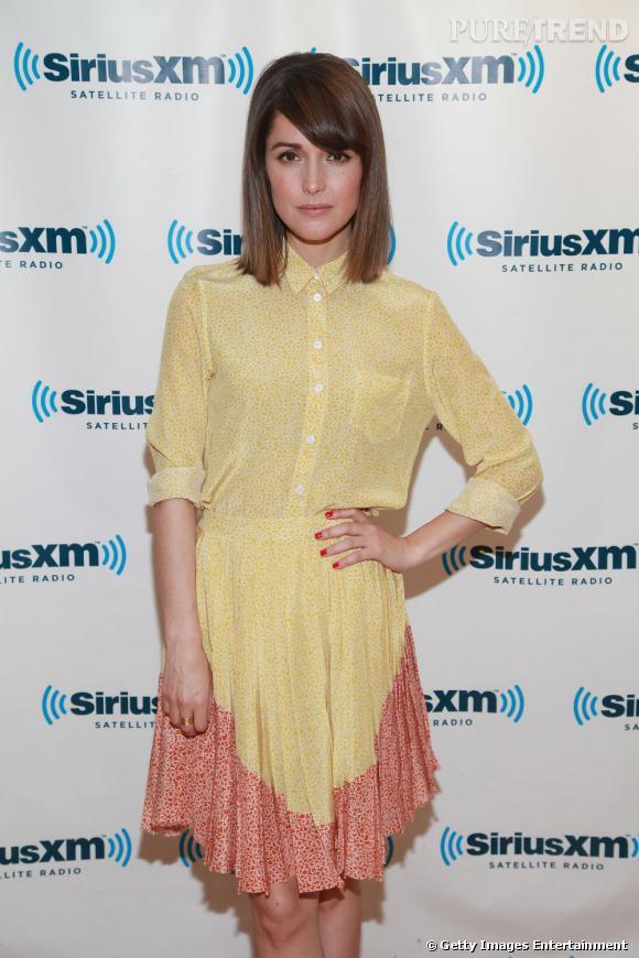 Rose Byrne opte pour une robe chemise jaune aux imprimés blancs et à la bordure rouge.