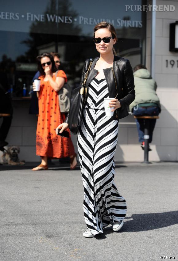 Olivia Wilde mixe la maxi-dress rayée avec une veste en cuir et des baskets Converse.