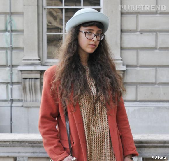 Les street styles beauté de la Fashion Week de Londres     Le beauty look de l'étudiante en goguette : lunettes sérieuses, frange, chevelure ondulée et chapeau. Rétro et décalé.