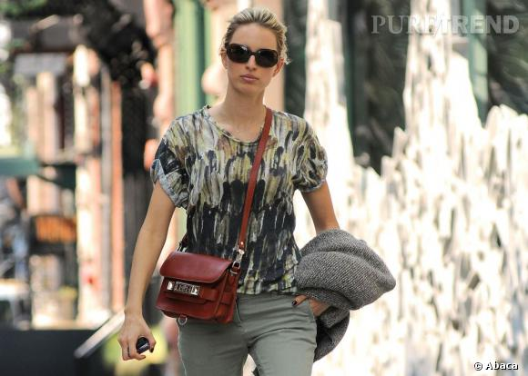 Karolina Kurkova twiste sa tenue avec un sac rouge brique Proenza Schouler.
