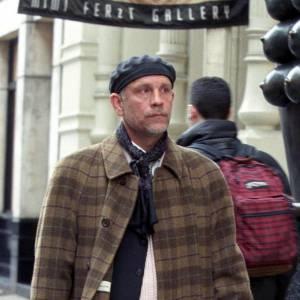 John détient un look de rue parfait : vêtu d'un long manteau imprimé de carreaux marrons, il met sur sa tête un petit béret noir et noue un foulard autour du cou.
