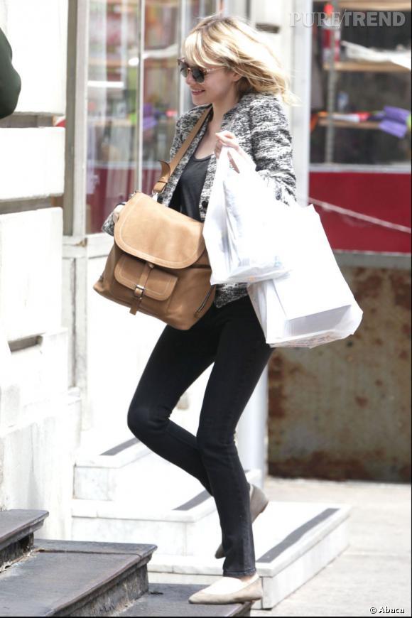 Emma Stone mise sur un skinny noir, un t-shirt sombre, une veste en camaïeu de gris et un sac beige.
