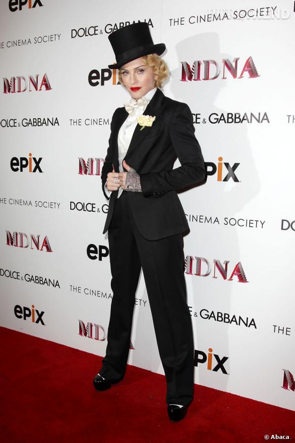 """Smoking large pour une touche boyish, noeud papillon en satin crème pour le côté doux, un rouge à lèvres vif pour le côté glam et une chevelure blonde crantée pour rappeler l'actrice Marlene Dietrich : la chanteuse a fait fort pour la première de son film """"MDNA : Tour""""."""