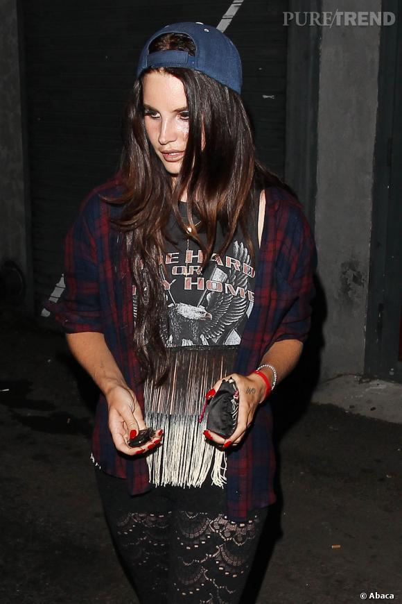 Lana Del Rey mise sur une chemise à carreaux, qu'elle enfile par dessus un t-shirt Harley Davidson à franges.