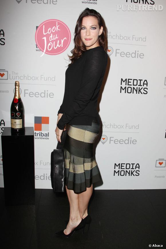 """Liv Tyler mise sur une jupe rayée dans des camaïeus de vert et sur un haut noir pour la soirée organisée par """"The Lunchbox Fund""""."""