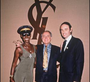 Grace Jones avec Pierre Bergé devant le logo Yves Saint Laurent.