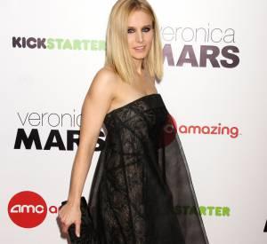 Kristen Bell complète sa tenue avec des escarpins compensés peep-toe et une pochette noire.