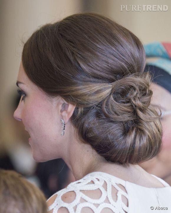 Quand Kate Middleton porte des chignons, il s'agit de modèles très travaillés. Une partie des longueurs est réunie dans un premier temps en un chignon bas et ancien, et les mèches de devant fixées par-dessus pour apporter un effet sophistiqué.