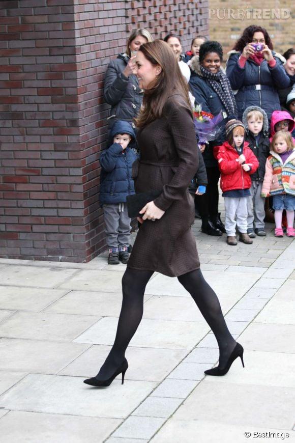 Kate Middleton dévoilant ses rondeurs de future maman dans une robe fluide et ceinturée sous la poitrine.