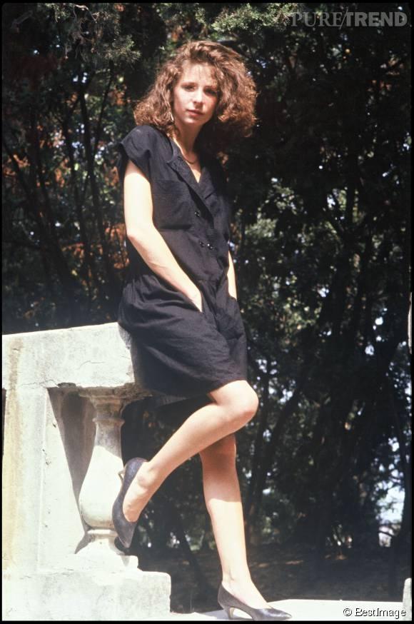 Mylène Farmer en 1985, robe noire sage et petits escarpins.