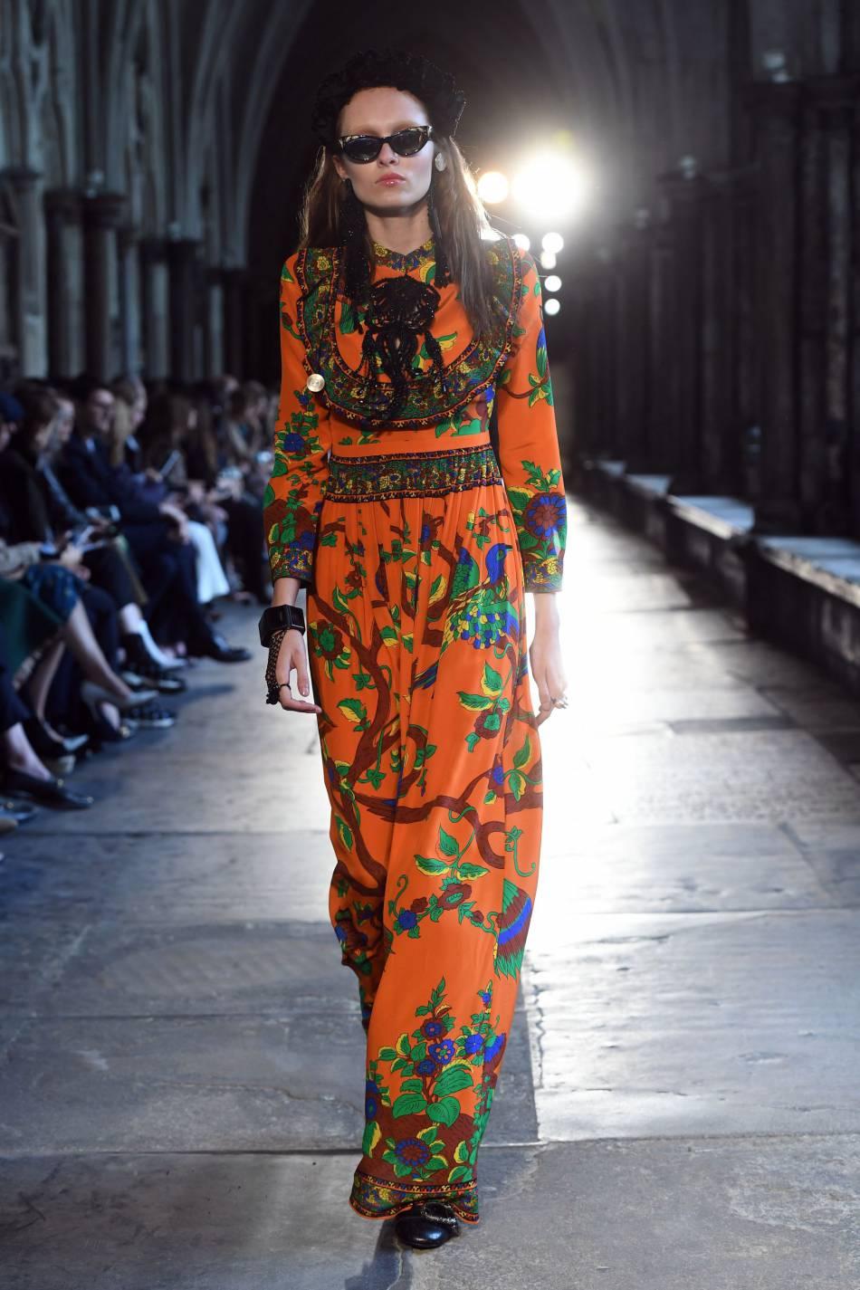 Une longue robe fluide imprimée ambiance Woodstock sur le défilé Gucci.