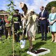 Kate Middleton, plantant un arbre lors d'une garde party, dans un manteau d'été beige.