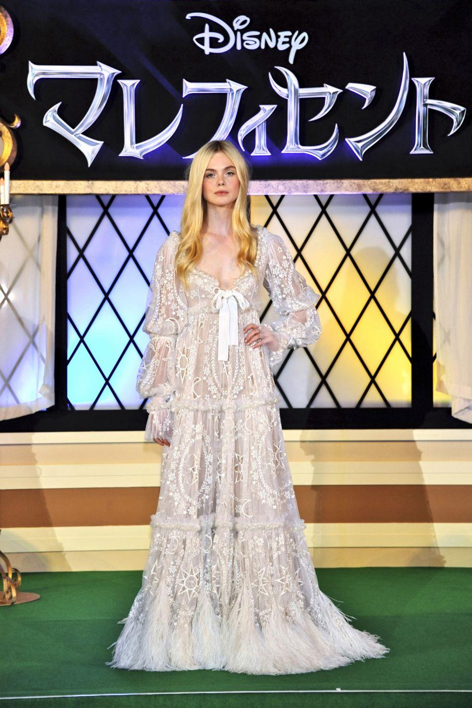 Elle Fanning portant une robe blanche longue ornée de perles.