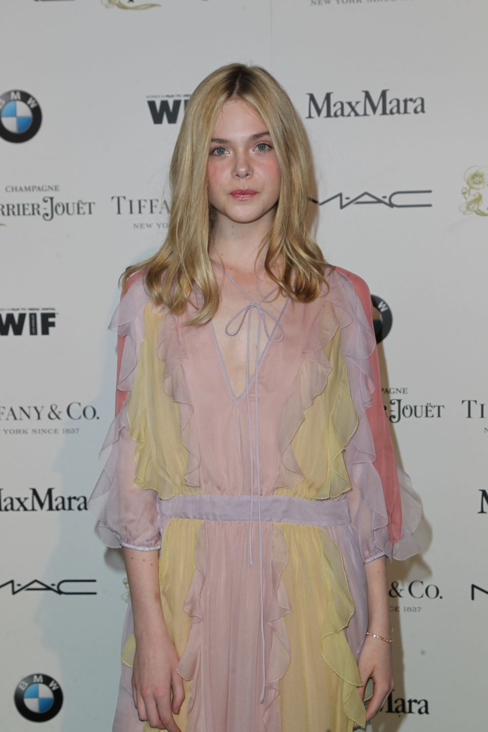 Elle Fanning, retour au blond, porte une robe au couleur pale, voilée.