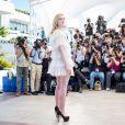 Elle Fanning posant au festival de Cannes dans une robe à volant blanche.