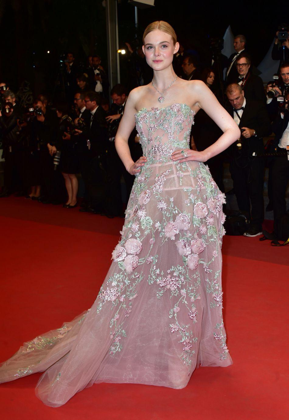 Elle Fanning habillée d'une robe bustiée rose ornée de fleurs et paillettes.