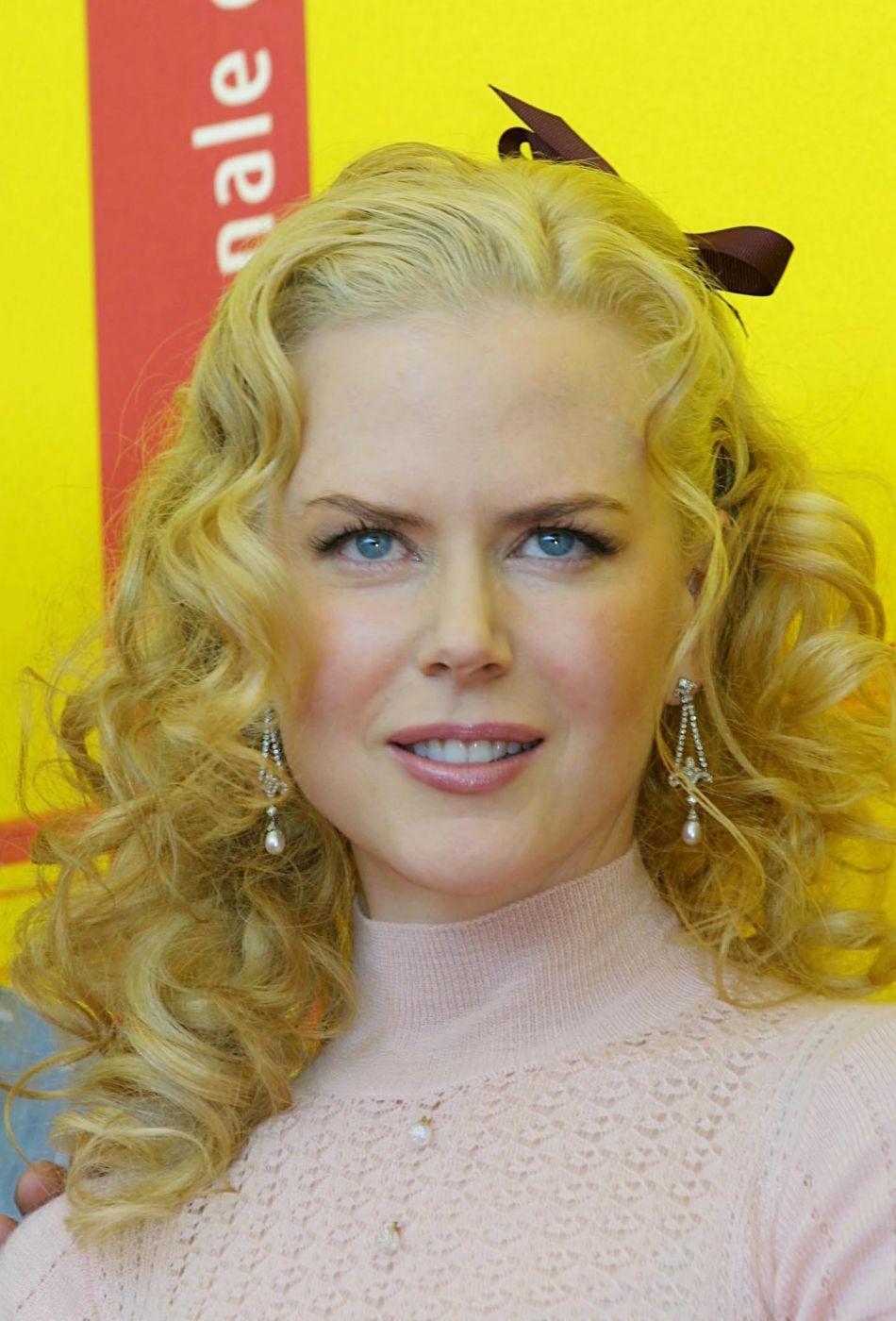 Joues roses (comme son top) et brushing bouclé, Nicole Kidman joue les filles sages à la 61e Mostra de Venise, en 2004.