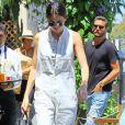 Kendall Jenner est vêtue d'une combinaison blanche en jean et accompagne sa tenue d'une paire de bottines noires en cuir vernis.
