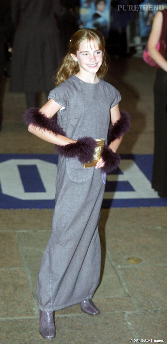 """A 11 ans, Emma Watson est encore une enfant à la première du film """"Harry Potter à l'école des sorciers"""". Perdue dans une longue robe grise, elle mime déjà les codes fashion avec un boa mauve autour des bras et une pochette dorée."""