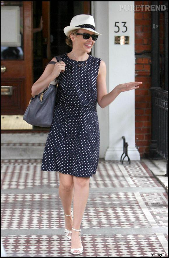 Kylie dans les rues Londres, habillée d'une petite robe à pois qui lui donne une allure sixtie's. Petites sandales à brides, borsalino, sac Downton  [brand=4294924524] YSL [/brand]  et Wayfarer de  [brand=4294959755] Ray Ban [/brand] , la star mise tout sur les accessoires.