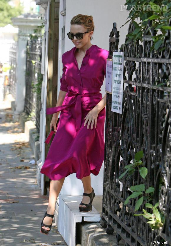 """La star ose les couleurs vives avec cette robe  rose """"shocking"""" ceinturée pour souligner sa taille de guêpe. Du haut de son 1,52 m, Kylie sait que pour porter une telle longueur de robe, il faut s'élever côté chaussures, comme avec cette paire d'escarpins à plateau  [brand=4294718939] Yves St Laurent [/brand] ."""