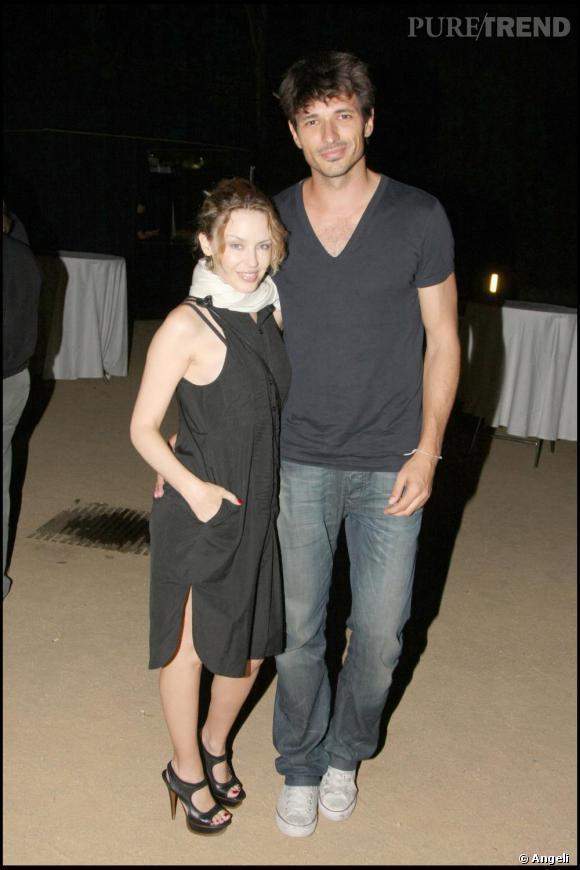 Kylie Minogue pose ici avec son nouvel amour, le top Andres Velencoso. Pour un dîner à Cap Roig sur la Costa Brava, elle joue la discrétion avec une petite robe noire sans manches. La belle ne quitte pas ses sandales à talons  [brand=4294718939] Yves St laurent [/brand] .