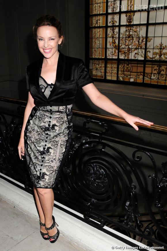"""Kylie Minogue, version """"fashion week"""" à Paris, lors du défilé Haute Couture  [brand=1379] Jean-Paul Gaultier [/brand] . Rayonnante dans sa robe   bustier en dentelle noire, la star ajoute une touche rock avec des escarpins  [brand=4294923135] Jimmy Choo [/brand]  cloutés et un boléro de satin noir."""