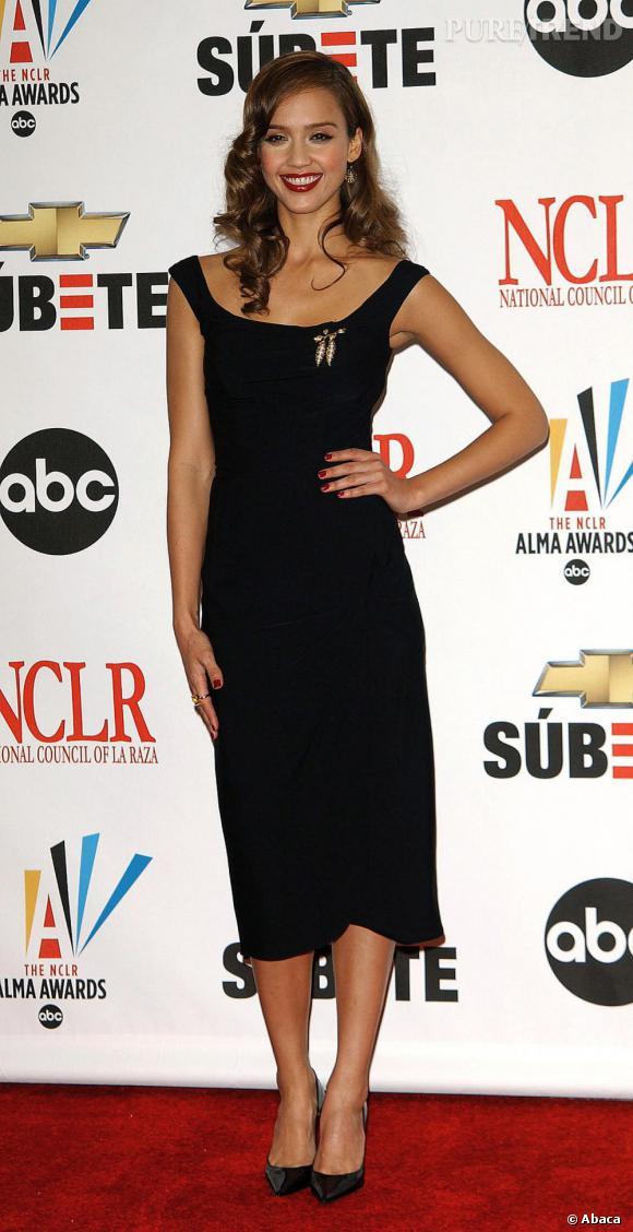 Rétro en robe noire au genou, longueur ô combien dangereuse qu'elle maîtrise à merveille.