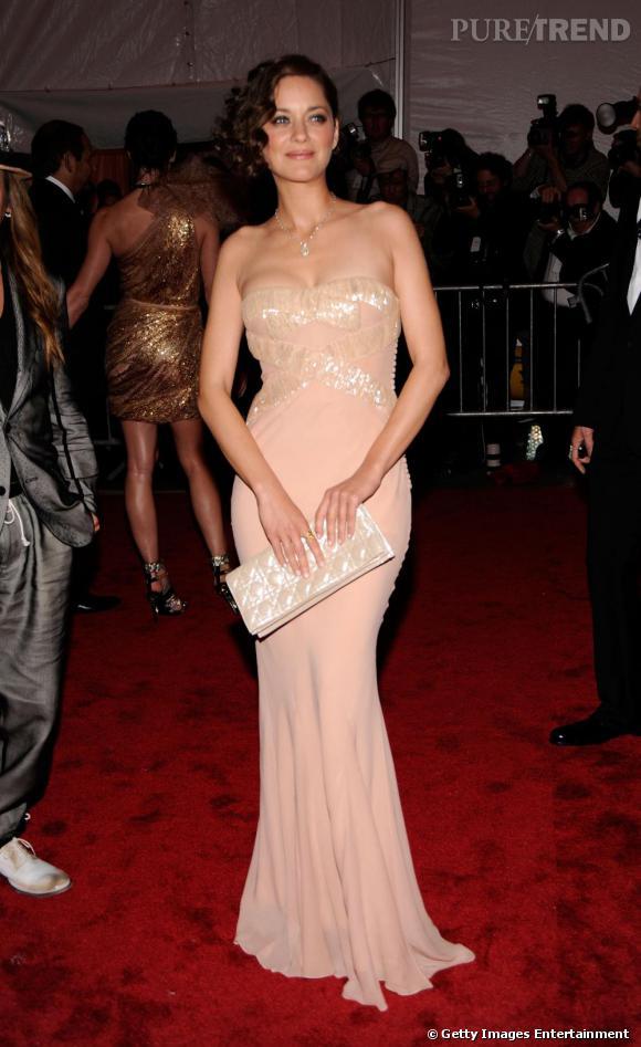Fidèle à la maison Dior, Marion Cotillard affiche une pochette vernis façon cannage, l'un des codes de la griffe.